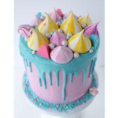Tuxedo cake with white chocolate raspberry buttercream, lemon and raspberry meringue kisses and chocolate candies