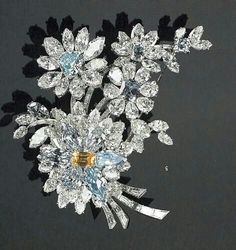 A diamond flower brooch containing numerous blue and white diamonds, plus one… Brooch Bouquets, Flower Brooch, Diamond Brooch, Diamond Jewelry, Colored Diamonds, White Diamonds, Selling Jewelry, Hair Ornaments, Jewelry Patterns