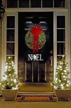 Elegant Christmas decor on a shiny black front door.