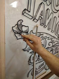 Sign writing the outlines on a gold leaf window sign