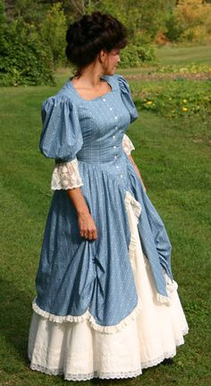 Charming calico dress has full Victorian styled sleeves and front button closure. The calico overskirt is shirred up and split in front revealing the attached lace trimmed underskirt.