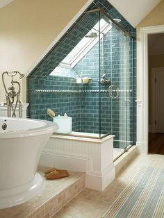 Loves! Teal-and-Beige Bath | Gorgeous teal tiles turn this under-the-roof shower surround into a stunning escape. Glass walls and doors allow the shower's beauty to be seen from any spot in the room, including the oversize soaking tub on a raised platform. Sand-color floor tiles and painted walls add a beachy vibe to the scene. A striped runner carries the beauty of blue throughout the space.