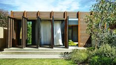 """<b>Facade</b> Off the master suite, a deck steps down onto a lush green lawn, which acts as a private zone. <a href=""""http://www.woodformarch.com/"""" target=""""_blank"""">Woodform Architectural</a> 'Concept Click' screening in blackbutt timber opens up to allow dappled sunlight into the indoor space."""