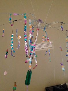 Love this chandiler made from an old umbrella.  The chandelier can tell a story of the class and involve parents to share memories to each strand.  Reggio inspired.