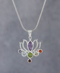 Cut out style lotus pendant is given radiant color and shine with Chakra inspired gemstones. Made of sterling silver and seven gemstones.