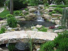 Backyard waterfalls, water garden, koi pond and streams, with stone bridge by Matthew Giampietro of Waterfalls, Fountains & Gardens Inc.