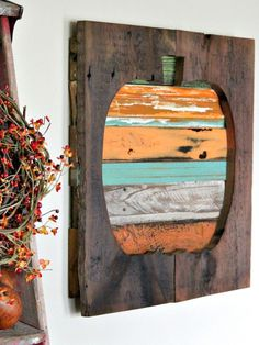 Reclaimed Wood Pumpkin - Some small scrap pieces of wood and a little reclaimed barn wood are all you need to create a colorful pumpkin wall hanging for fall. #…