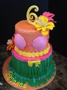 This is a luau birthday cake, for a 6th year old, with a sea shell bra, and a grass skirt, with flowers
