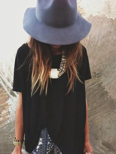 black top, bold necklace, printed shorts, felt hat