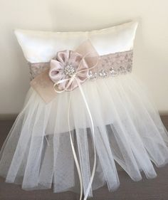 This listing is for:    (1) Ivory/Champagne Ring Pillow    Ivory satin ring pillow wrapped in a delicate champagne ribbon and sequined lace.