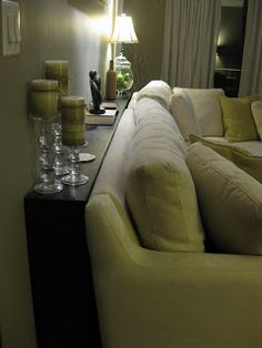I like to place a narrow table behind a sofa when the sofa is in a big room creating a separate area for seating. If you have a special collection you can display a few items on the table for a conversation starter and for personal 'comfort!'
