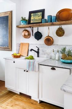 An apron sink, one-handled faucet and hand-planed wood shelving give this kitchen a farmhouse feel. | Photo: Andrea Rugg | thisoldhouse.com
