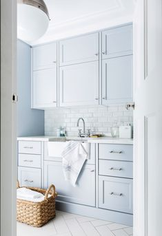 A powdery duck-egg blue colour scheme has a calming effect in this Hamptons-style laundry designed by Coco Republic to suit an Art Deco-style home | Photo: Maree Homer