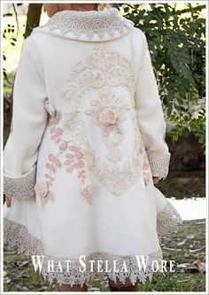 Coat embellished on back with large lace medallions, painstakingly sewn around the major details with metallic silver thread, and then cut away in the center. Pink leaves, cut from a piece of lace and appliqued on. Rosebuds created from 100% wool felt, dyed the palest pink and hand-formed. Pink beaded leaf details.