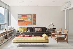 A mesa de centro vermelha (modelo Ômega, da 021) traz vibração ao ambiente, que tem sofá de linho marrom (JRJ) e poltronas Samy, da Interni. Na parede, a tela maior é de Marcus André (Galeria Contorno).