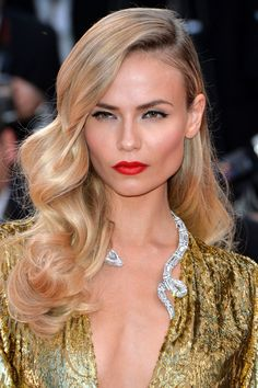 How to get Natasha Poly's glamorous beauty look—from the waves to the orange-red lipstick.