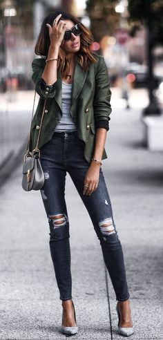 Khaki jacket over gray tee and blue jeans.