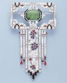 AN ART DECO EMERALD AND DIAMOND BROOCH. The central octagonal emerald within an onyx and diamond surround to the openwork rectangular panel and diamond fringe with cabochon sapphire and ruby floral detail and onyx terminals, circa 1925.♥≻★≺♥
