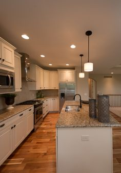 Acacia hardwood flooring, granite counters, island with eating bar, white painted cabinets, stainless appliances