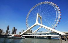 Tianjin Eye in China~If there's a country where Ferris wheels are spinning into the future, it's China. Take for instance, the sci-fi worthy TianjinEye. The 394-foot wheel straddles a bridge & is the world's fourth-tallest. Changsha Ferris Wheel, Suzhou Ferris Wheel, and the Zhengzhou Ferris Wheel are similarly gargantuan Chinese attractions. All of these structures,however,are dwarfed by the mind-bending 525-foot span of the Star of Nanchang. Only the Singapore Flyer reaches higher in the w...