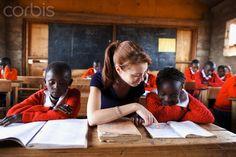 Teacher reading with school children in classroom, Kenya