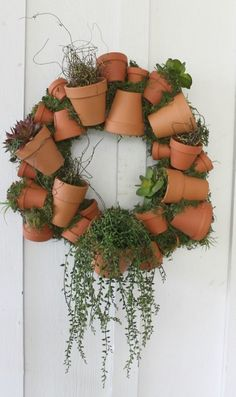 Turn your door into a cute garden with this wreath made of small planters.