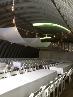 Market lights, fabric and pipe and drape treatment transform a Quonset into a wedding reception
