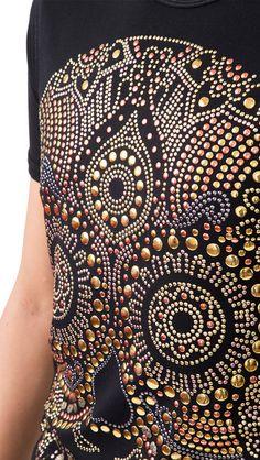 Playera de caballero cuello redondo, corte a siluetado, mas largo de la espalda. La tela permite la libre transpiración del cuerpo y su base sintética ayuda a evitarlas arrugas de la prenda. La calavera está formada con piedras metálicas de diferentes colores y tamaños que dan un efecto 3D, detallando los dientes, pómulos y barbilla.      Técnica: Aplicación de pedrería por medio de calor.  Composición tela: 95.2% Viscosa - 4.8%Elastano.  Cuidados de la prenda:Se debe lavar…