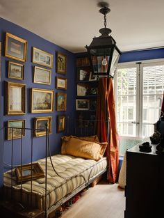 Room of the Day ~ In the blue guest bedroom a collection of paintings and treasured pieces from travels is displayed above the iron bedstead. Love the lantern and deep blue walls, orange drapes. Beautiful Bedrooms, Interior, Blue Rooms, Home, Home Bedroom, Bedroom Design, House Interior, Interior Design, Rustic Bedroom