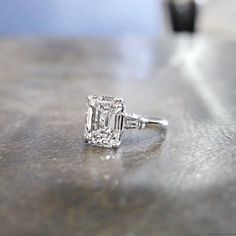 HALLE is a custom, three stones engagement ring set in Platinum with an Emerald cut diamond and two tapered baguettes, from jewelry designer Jean Dousset.