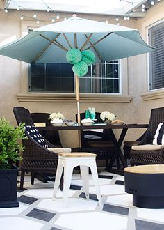 The umbrella, string lights, painted floor, fire pit... there's so much to love about this small patio. (Yes, there's a fire pit in this photo.) Click through to see how blogger Brittany of brittanyMakes refreshed the look of her outdoor space.    @brittanymakes