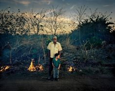 Fidel Hernandez sets fire to the bushes around the fence he just installed to keep his goats enclosed. He has taken his grandson with him, as he says that he loves to hang around his grandpa.