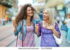 two teen woman friends having fun and eating ice cream - stock photo