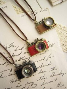 camera necklaces. LOVE. You know, this would be a great birthday present.....;]