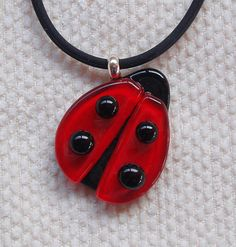 This cute pendant representing a ladybird is made of glass. Its body is black, its wings red with four small black balls. The ladybug is approximately 2.5 cm wide x 3 cm long and 4 mm thick. It was shaped according to the fusing technique. The bail is also handmade in sterling silver guaranteed by my hallmark This pendant comes with a 46 cm black rubber cord with an easy and secure clasp. Symbol of luck and happiness ...