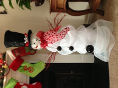 Cracker Barrel snowman head with deco mesh wrapped around large glass vase. Ornaments for buttons and decorative twigs from Michaels attached with wire for arms. Took about an hour. I think it turned out ok. ?!? *