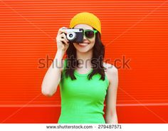 Fashion, summer and people concept - pretty cool girl in sunglasses with retro camera having fun against colorful red wall