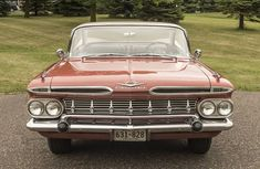 "1959 Chevrolet Impala 2 Door Hardtop; the ""V"" on the hood indicates a V-8 and the crossed flags indicate the 348CI engine"