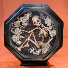 Original skeleton in an antique clock case with memorial flowers made of feathers. © Rucus Studio 2014