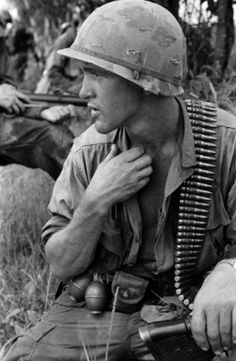 "Charlie Haughey's Vietnam Reels | ""An M60 operator pauses for a moment under the heavy load of machine gun ammo. Members of the unit were all required to carry some type of ammo or supplies, including bandoliers of heavy bullets. Name, date, and location unknown."""