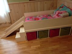 DIY toddler bed with small slide and toy storage.