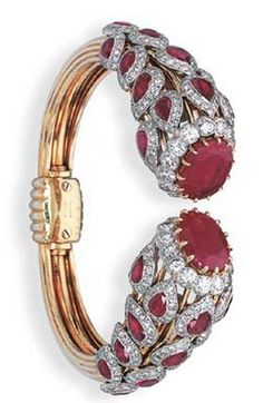 AN ELEGANT RUBY AND DIAMOND BANGLE, BY CARTIER Designed with oval-cut ruby and brilliant-cut diamond cluster terminals to the drop-shaped cluster and openwork shoulders, circa 1955, 5.8 cm. diameter, with French assay mark for platinum and gold Signed Cartier Paris, no. 08289, accompanied by original Cartier stock photograph