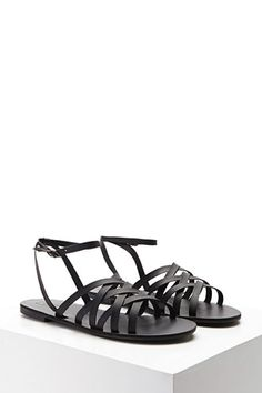 A pair of faux leather sandals featuring a strappy design with stud accents, high-polish buckle, an open-toe, and a low heel.