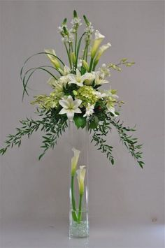 Few fresh cut flowers offer the elegance and versatility of the calla lily. If you are designing your own wedding bouquet, centerpieces or arrangements, the calla lily will provide all of the style… Altar Flowers, Church Flower Arrangements, Church Flowers, Funeral Flowers, Flowers Vase, Tall Floral Arrangements, Lilies Flowers, Tall Flowers, Tall Wedding Centerpieces