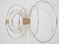 inspired by hoop skirts from the early 1900s, brass hoops cast light from small tabs which act as handles: Ring of Fire by Elish Warlop