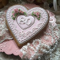 80th birthday keepsake, heart cookie piped exquisitely with oodles of perfectly delicate lace and pink roses. The numerals are piped in a lovely vintage embroidery design. This cookie is breathtaking in its delicate beauty.