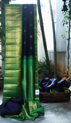 FETCHING NAVY BLUE KANCHIVARAM SILK WITH BUTTAS ALL OVER HAS STRIKING GREEN WITH GOLD ZARI BORDER AND PALLU MAKES THIS SAREE MAGNIFICENT. THE SAREE COMES WITH DUAL BLOUSES TO CHOOSE FROM NAVY BLUE ...