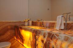 Lavabo em onix, piso, bancada e roda meio. Um luxo! By Marina Salomão Arquitetura e Interiores.