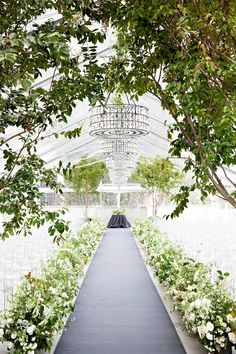 """For this wedding, Steven Moore aimed to create """"an amazing secret garden,"""" and that's exactly what this couple got. The stunning ceremony tent featured green-and-white flower arrangements, plus six 12-foot maple trees that are now planted at the bride's parents' home."""