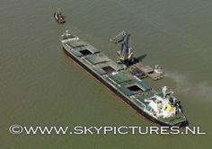Kraan van OVET Terneuzen lost op de Westerschelde een bulkcarrier